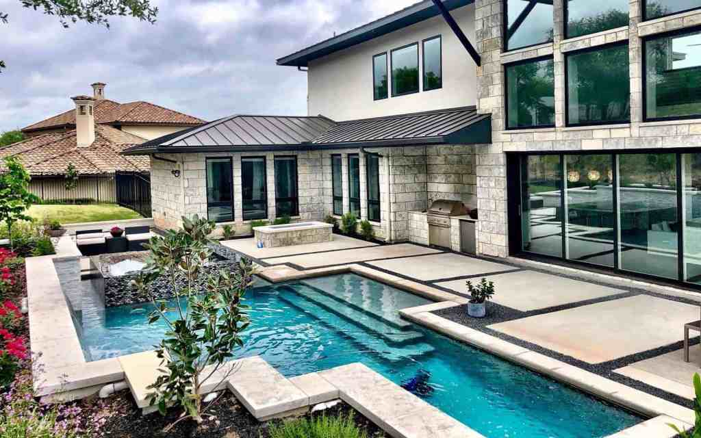 Pool and spa combo with waterfall. Kitchen area is designed into the deck and side of home.