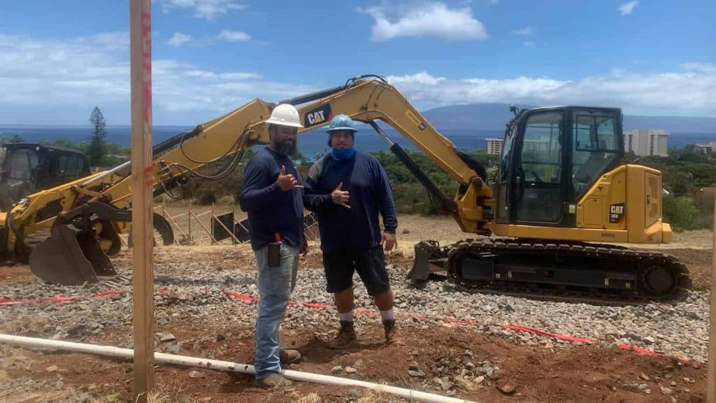 Excavator and employees at new home site on Maui