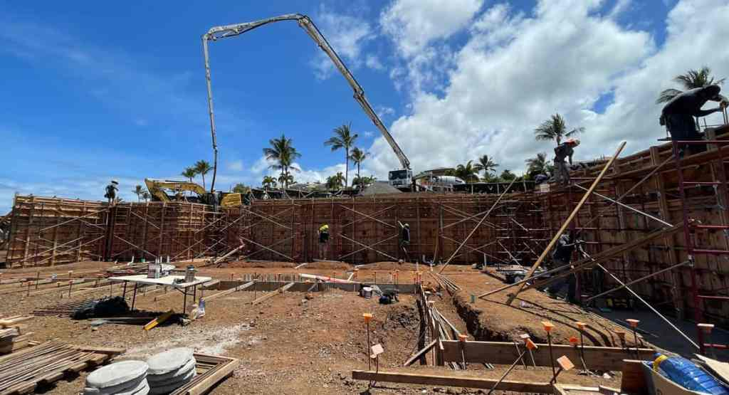 Image of a crane pouring concrete for a home's first floor 12-foot concrete retaining wall