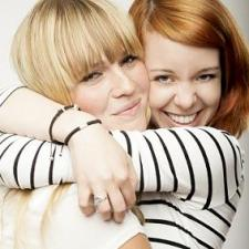 red and blond haired girls laughing and hug