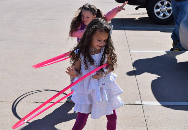 Young girls in Easter Sunday dresses doing the hoola-hoop in the parking lot.
