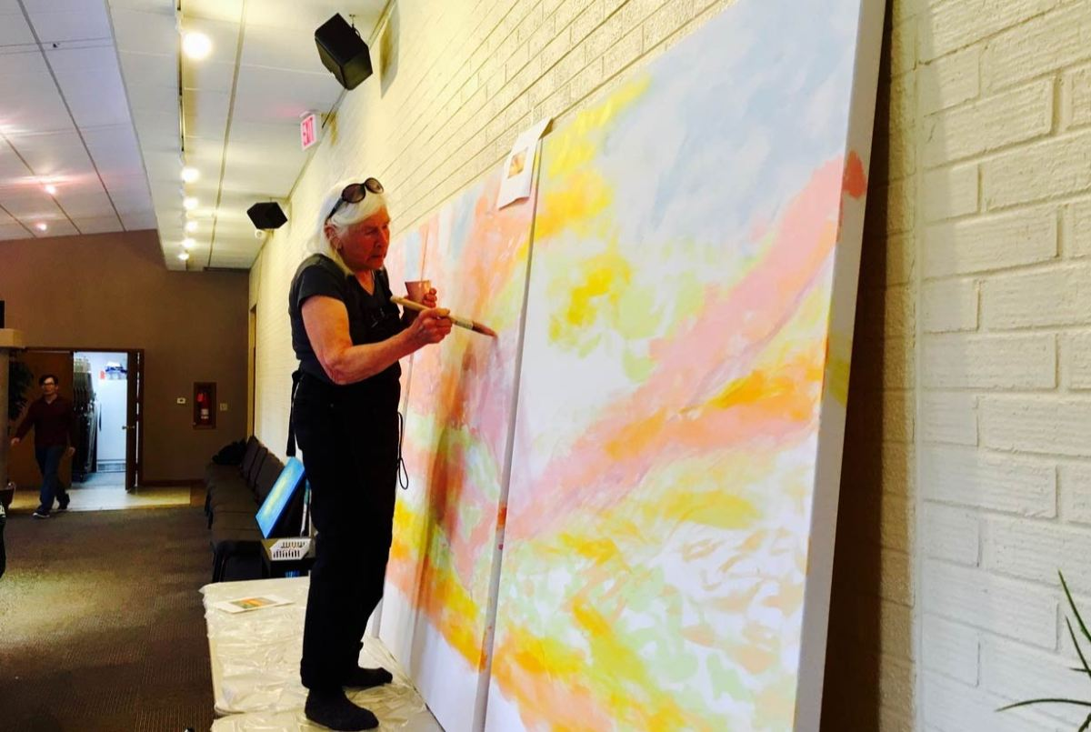 Photo of Ruth Neibur painting a glorious sunrise on a large canvass for Easter Sunday, 2017.