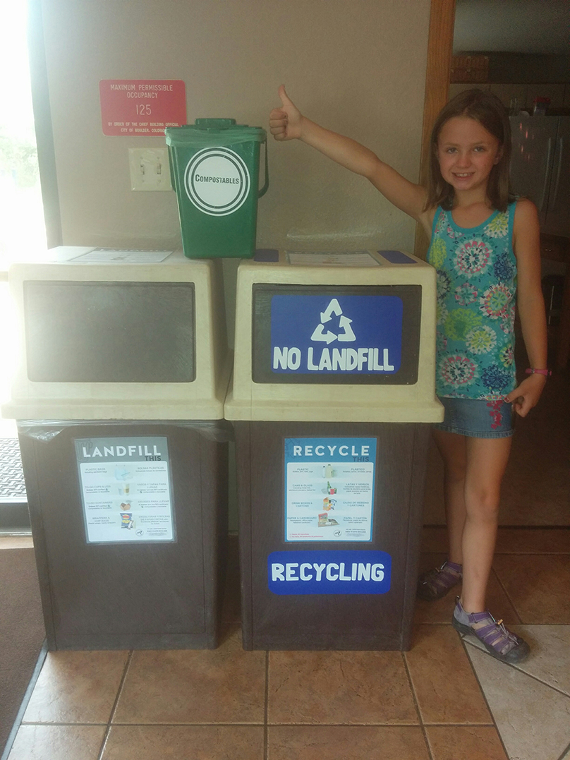 Anna standing by recycle and compost bins giving the thumbs up for Crestview's Zero Waste Initiative.