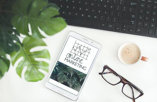 Blog post on Pinterest growth. Image has objects on a desk, including a pair of glasses, a keyboard and a phone with a screen display of a graph.