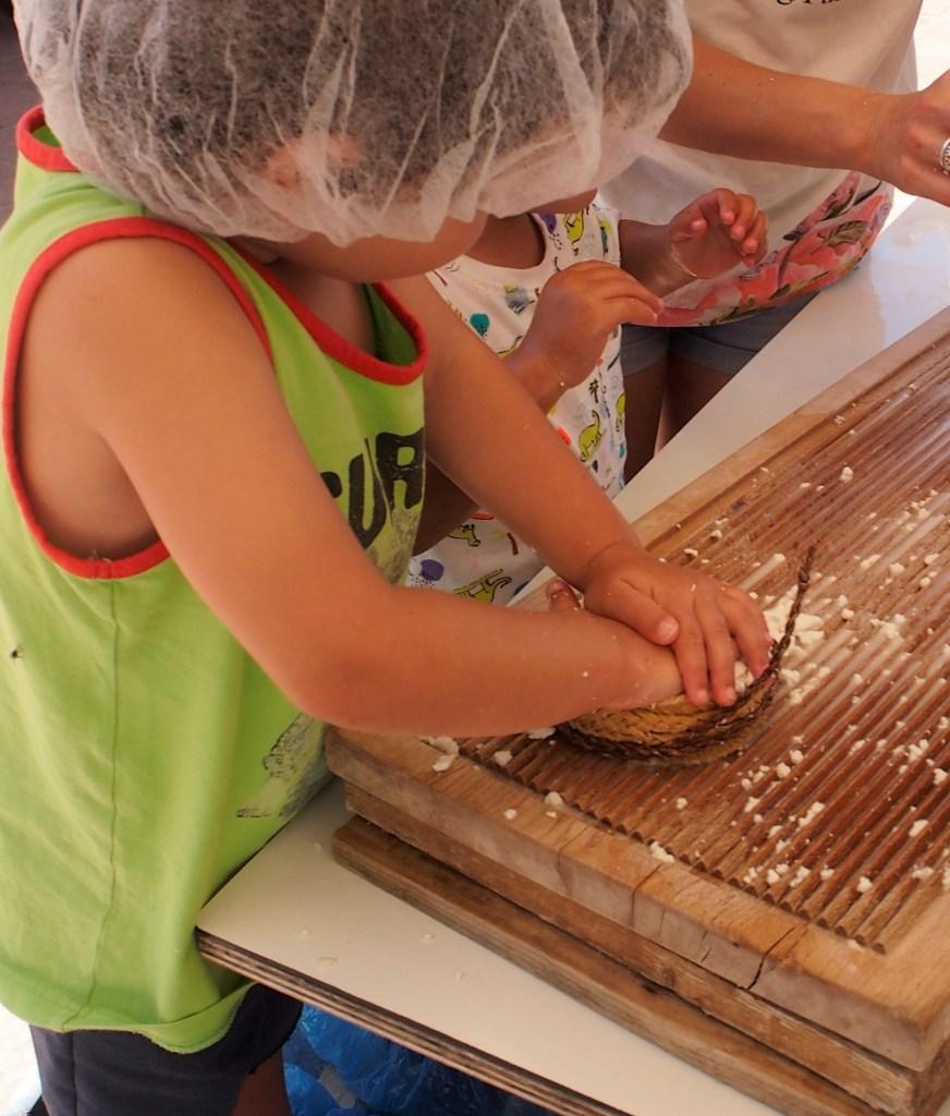Niños prensando queso con sus manos