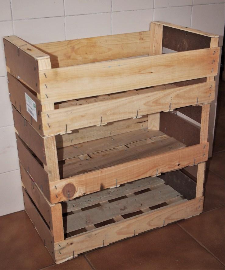 3 cajas de calabacín apiladas con una parte del frente quitada y que parecen un mueble de madera