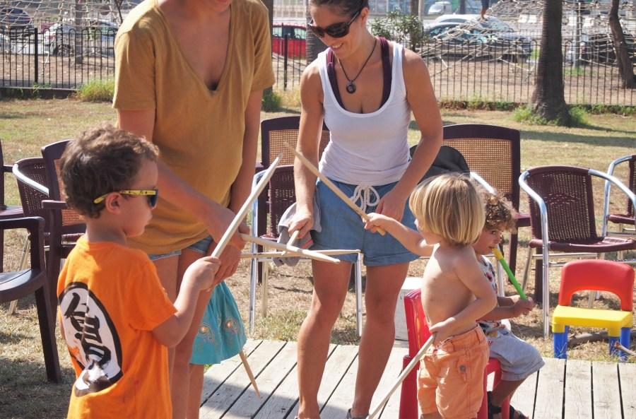 Niños tocando baquetas en el taller de música en el parque