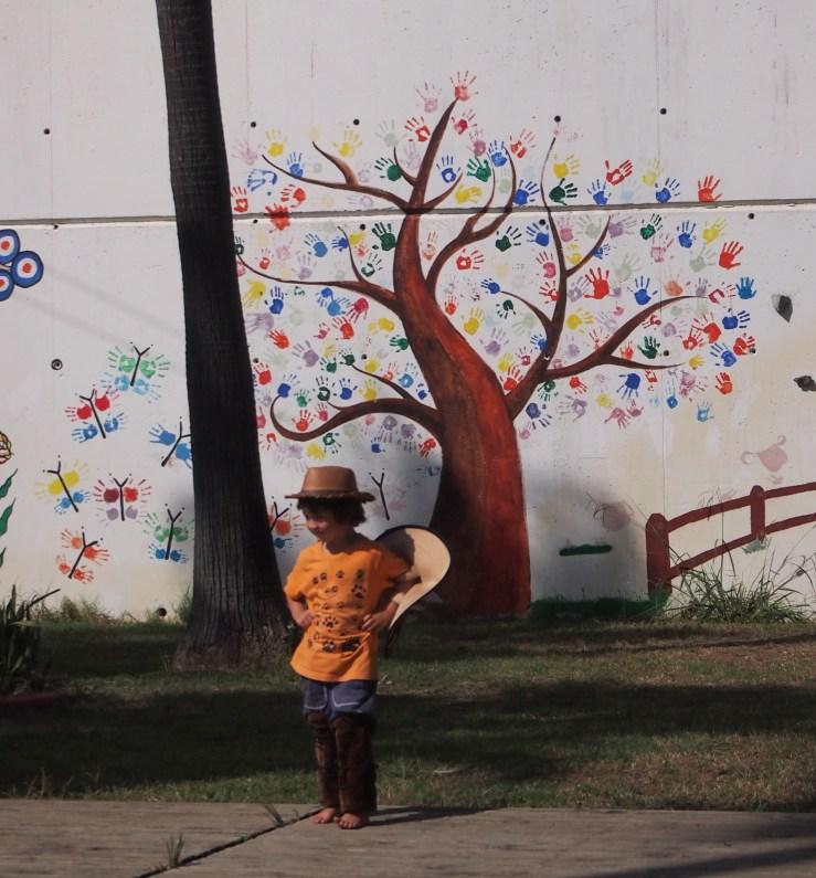 Niño disfrazado y grafiti con arbol de manos detrás