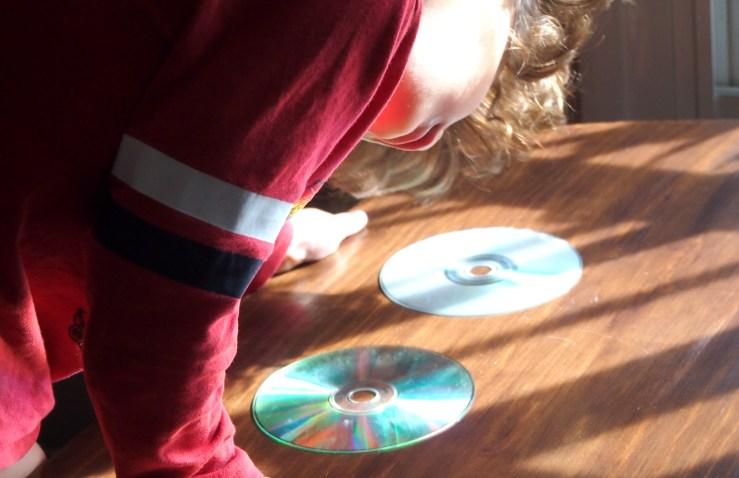 Nico observando la luz y los reflejos en los Cds