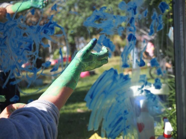 Mano y brazo de niño pintada con el reflejo del espero detrás