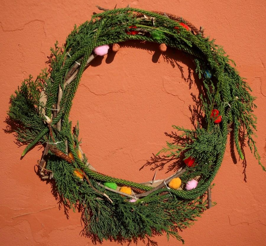 Corona verde hecha de plantas y palos y decorada con pompones.