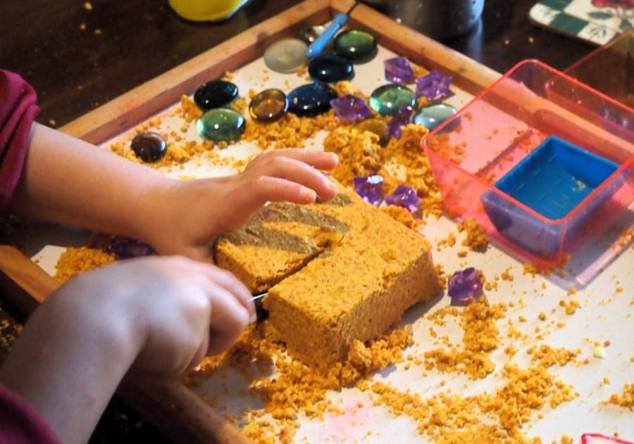 Manos de niños cortando una tarta hecha de arena magica de madarina