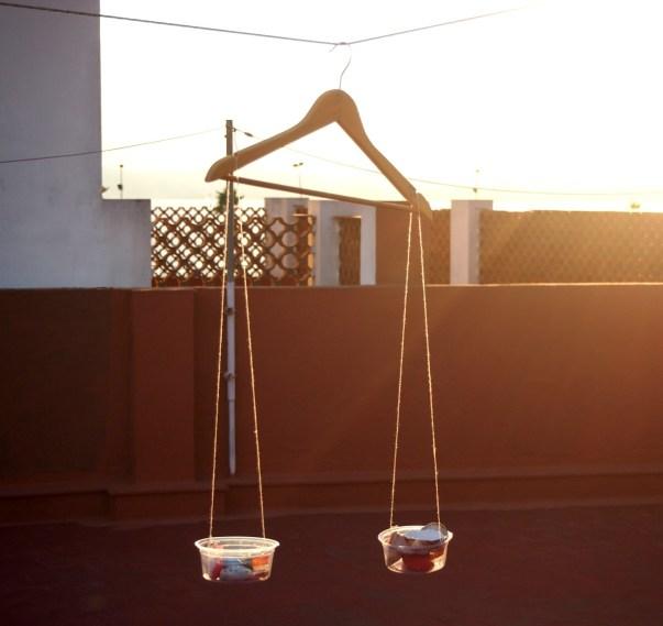 Foto de una balanza hecha con una percha y dos boles colgados