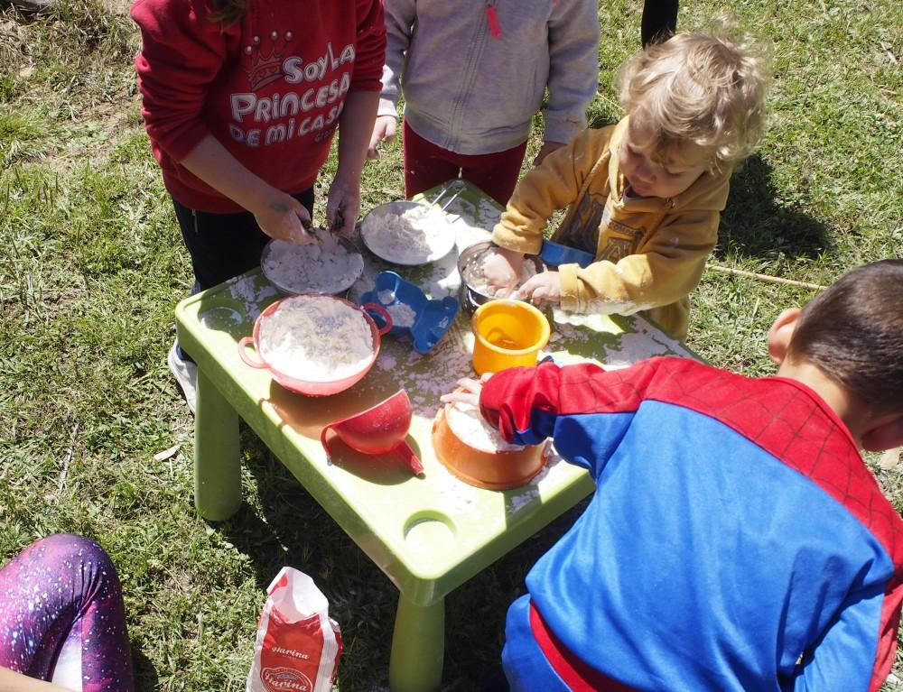 Niños jugando con la harina y cacharritos en una mesa en el parque