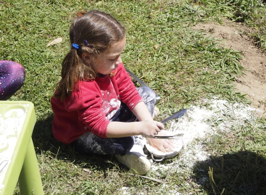 niña muy concentrada jugando con la harina en el cesped. Grupo de juego Sintiendo el parque