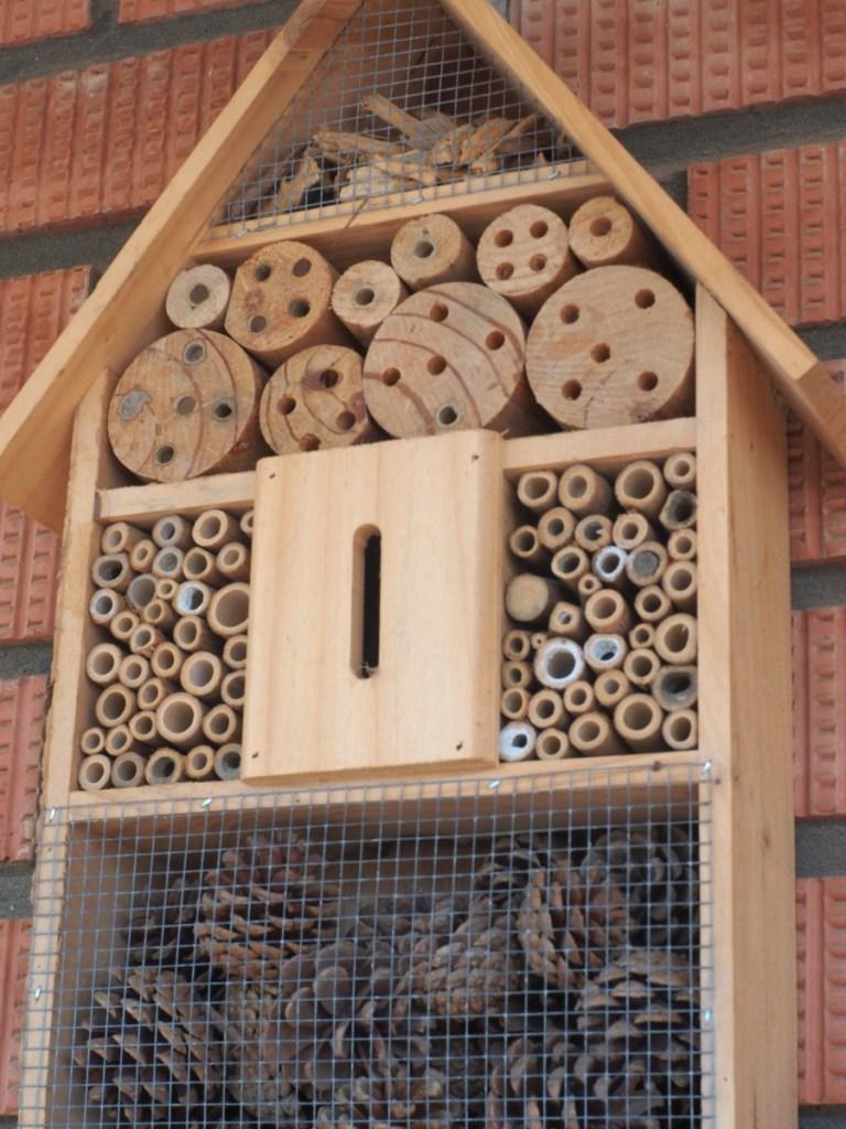 Hotel de insectos comprado donde se ven las cañas y las maderas con agujeros asi como piñas y maderas