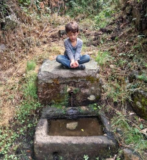 Niño con moras en mano encima de una fuente de piedra