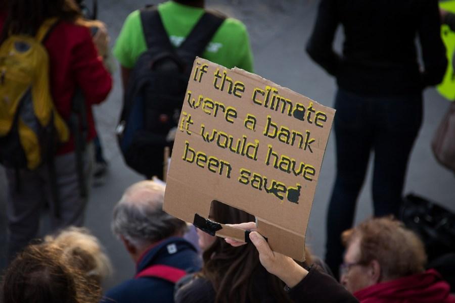 """Pancarta que dice: """"si el clima fuera un banco ya lo habrian salvado"""""""