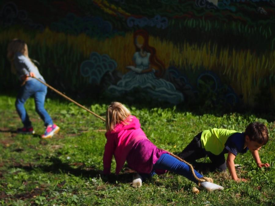 Niños y niñas jugando con una uerda arrastrandose por el suelo unos a otros