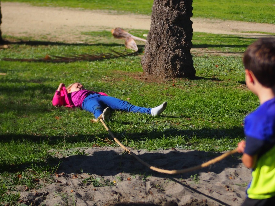 Niña tirada en el suelo riendo después de caerse al suelo jugando con cuerda
