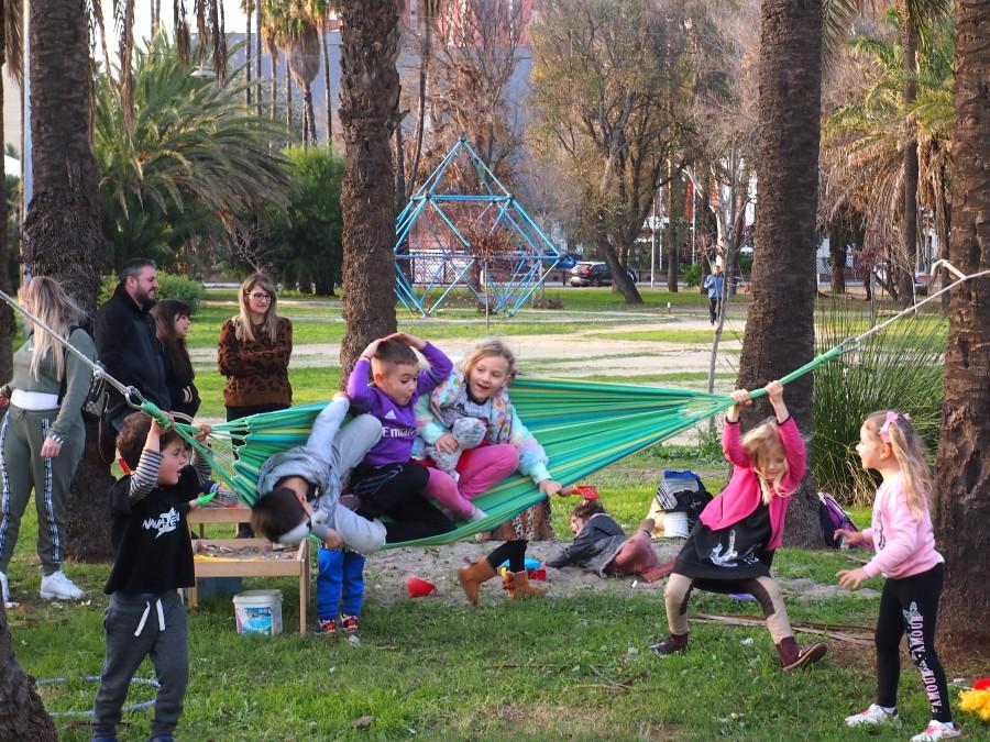 Niños y niñas jugando en una hamaca. Familias observando de fondo, una de las normas del grupo de juego es acompañar y cuidar