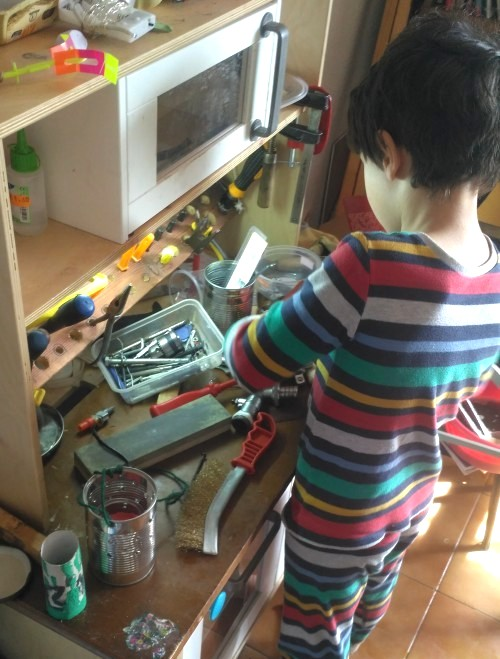 Un niño trabajando en un min taller convertido de cocina de ikea