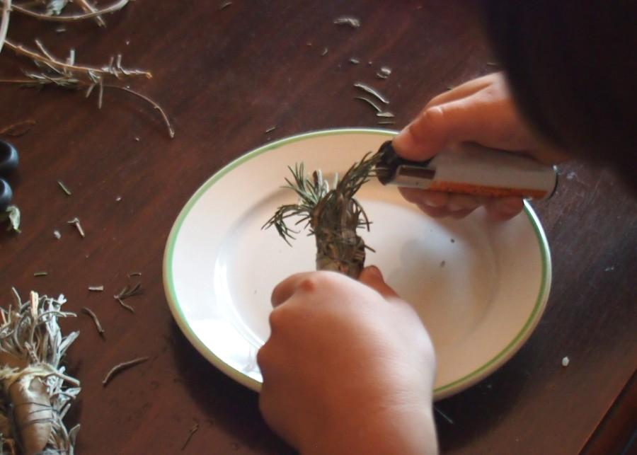 Manos de niño encendiendo un atado de hierbas para sahumerios