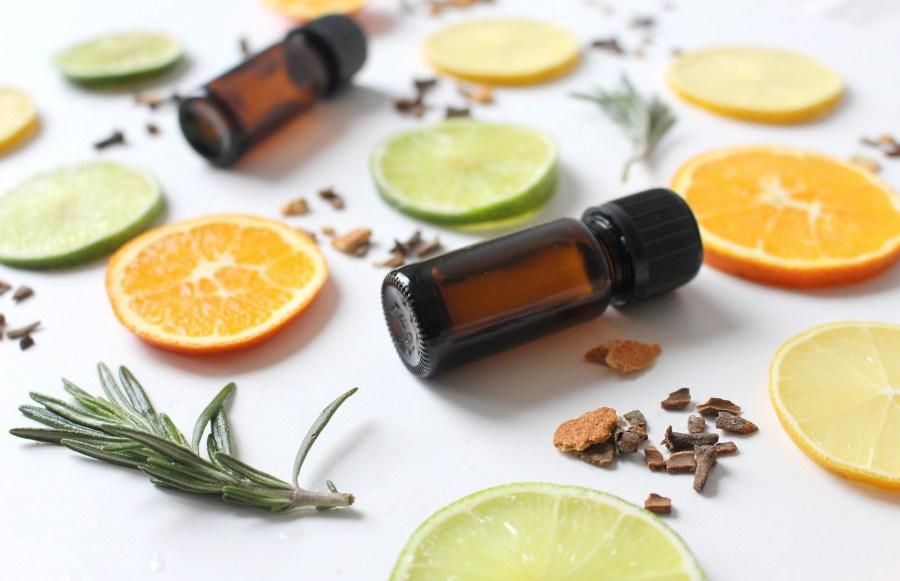 Bote de cristal de aceite esencial con trozos de citricos y romero al rededor