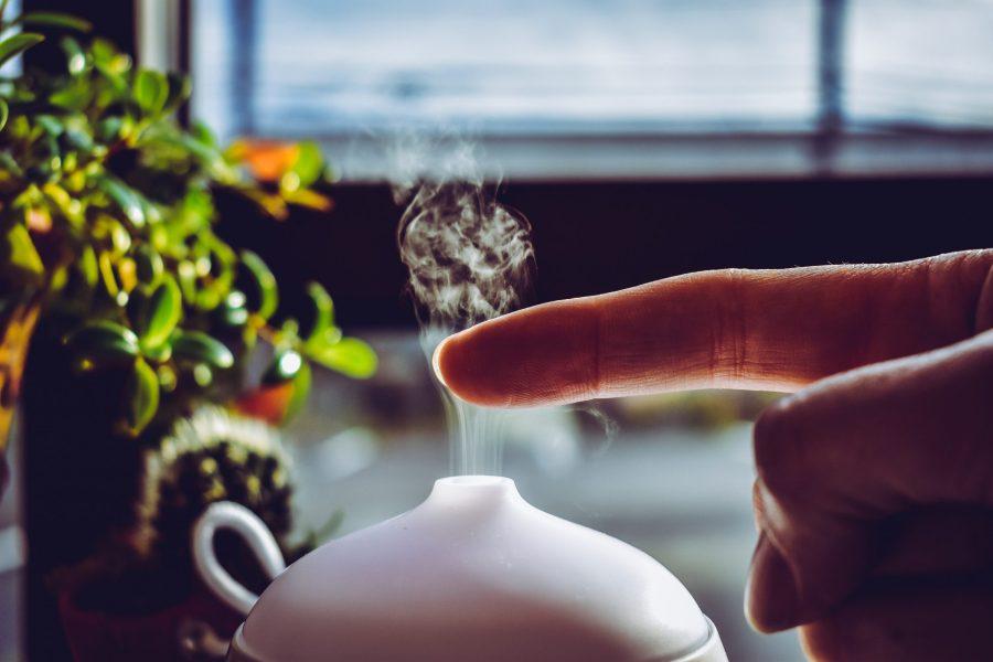 Un dedo encima de un difusor de vapor para sahumerio de aceites esenciales