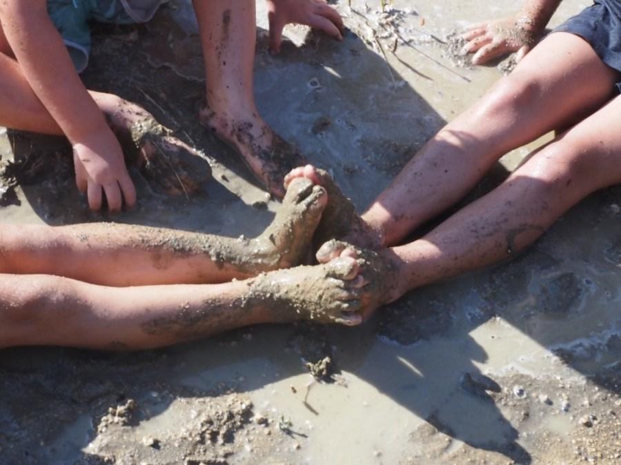 Pies de niños pringados de barro en un charco