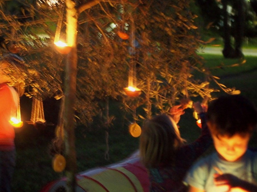 Ninos y niñas mirando velas alrededor de un árbol de navidad decorado en un parque