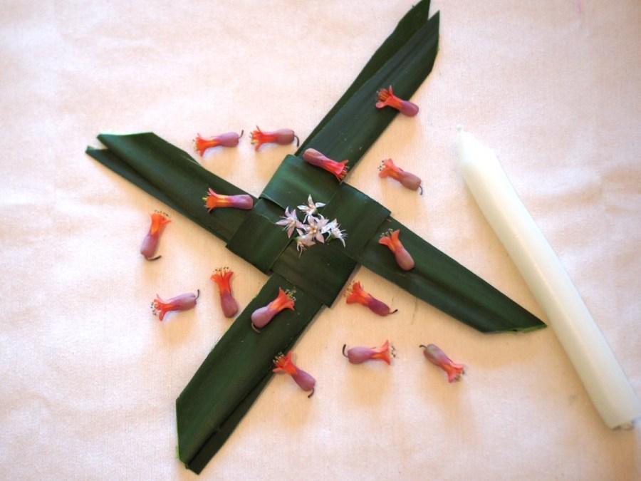 Cruz de Brígida hecha con hojas de palmera y decorada con flores