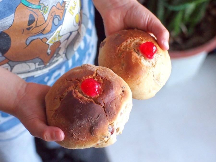 Manos de niño sugetando dos panecillos dulces con forma de teta