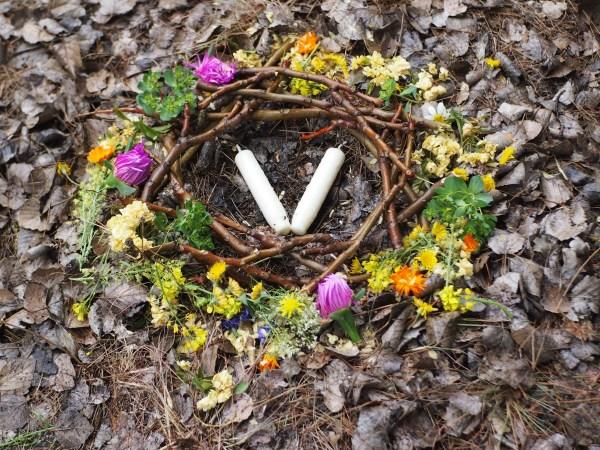 Foto de un pequeño nido rodeado de flores y con velas en el centro representando la energía de Beltane o los mayos