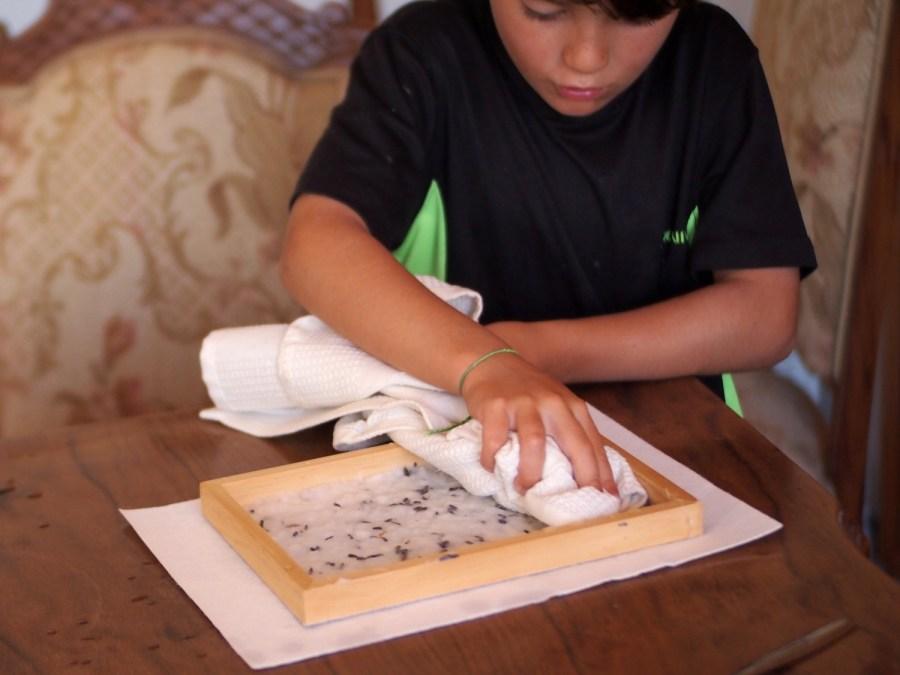 Niño secando el papelcasero con semillas