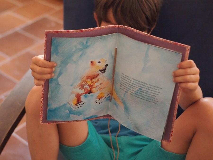 Niño mostrando su cuento personalizado donde se ve una ilustracion de un oso