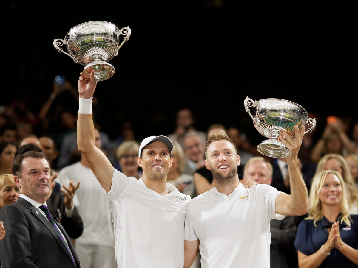 Mike Bryan, left, and Jack Sock of the US hold up their trophies after defeating South Africa's Raven Klaasen and New Zealand's Michael Venus in the men's doubles final match at the Wimbledon Tennis Championships, in London