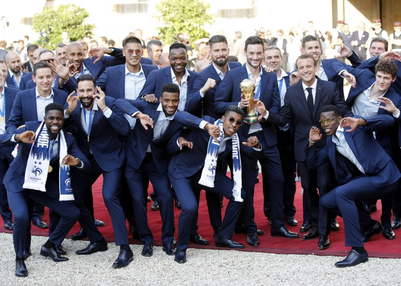 French President Emmanuel Macron, third right, third right, poses with the French soccer players at the presidential Elysee Palace after the parade down the Champs-Elysees