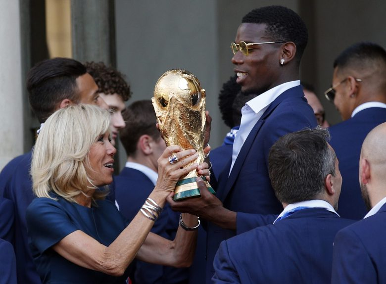 French player Paul Pogba lifts the cup with Brigitte Macron, wife of French President Emmanuel Macron, at the Elysee Palace