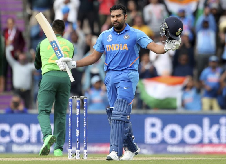 India's Rohit Sharma raises his bat and helmet to celebrate scoring a century