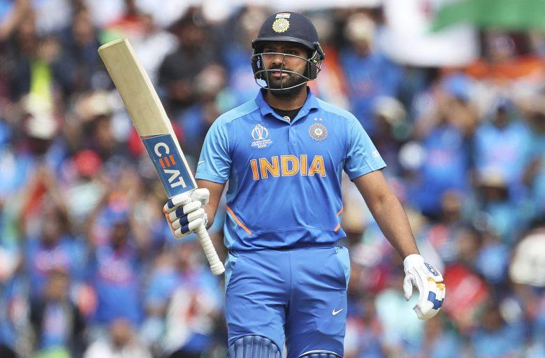 India's Rohit Sharma raises his bat to celebrate scoring fifty runs