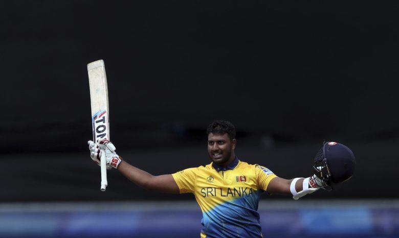 Sri Lanka's batsman Avishka Fernando raises his bat and helmet to celebrate scoring a century