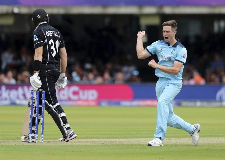 England's Chris Woakes, right, celebrates the dismissal of New Zealand's Martin Guptill, left