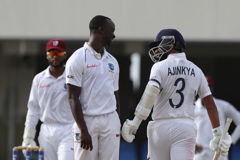 West Indies' bowler Kemar Roach, left, and India's Ajinkya Rahane talk
