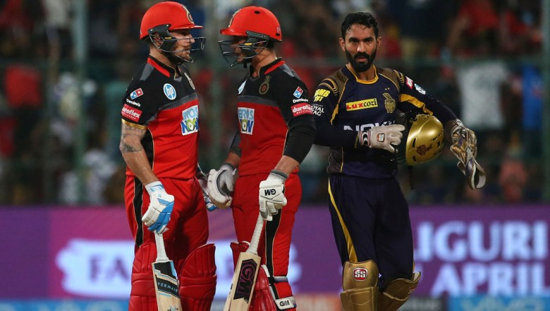 Kolkata Knight Riders' captain Dinesh Karthik, right, walks past Royal Challengers Bangalore batsmen Brendon McCullum, left, and Quinton de Kock at the end of an over