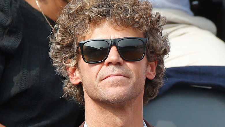 Three-time French Open winner Gustavo Kuerten of Brazil watches the men's final match of the French Open tennis tournament at the Roland Garros stadium in Paris