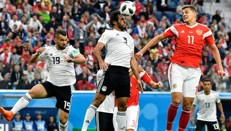 Egypt's Marwan Mohsen, center, and Russia's Roman Zobnin, right, go for a header during the group A match between Russia and Egypt at the 2018 soccer World Cup in the St. Petersburg stadium in St. Petersburg
