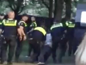 Agenten slepen de man, die niet meer op zijn eigen benen kon staan, richting het busje.