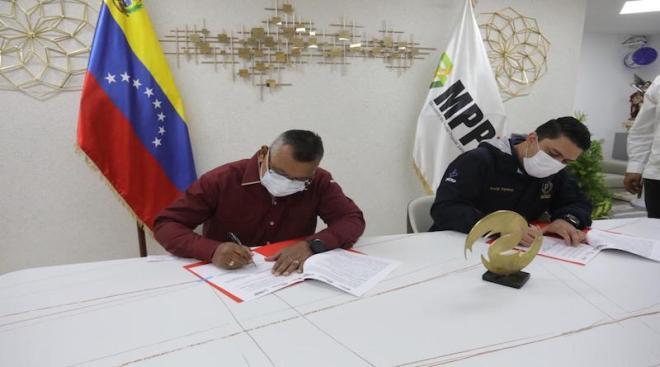 El ministro de energía, Néstor Reverol (izquierda) y el supertintendente de criptomonedas, Joselit Ramírez (derecha), firman acuerdo que excluye a los mineros del subsidio eléctrico que gozan los venezolanos. Fuente: VTV