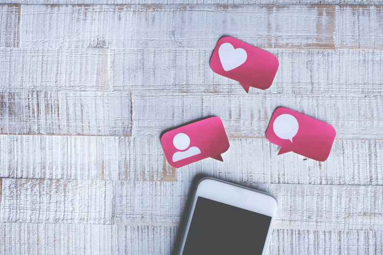 A smart phone against a white textured wall. There are three red speech bubbles: one with the heart icon, one with the speech icon, and one with the person icon.